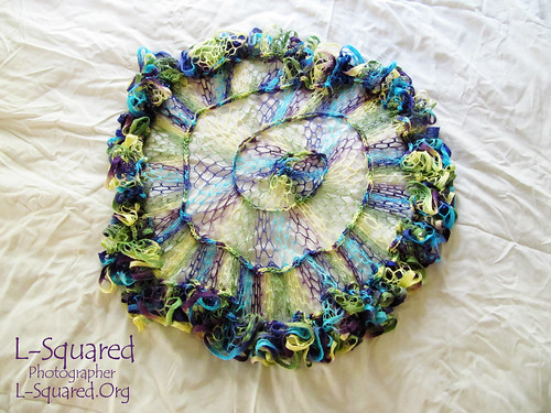 Circular, spiraled mesh shawl in hues of yellow, green, teal, blue and purple.