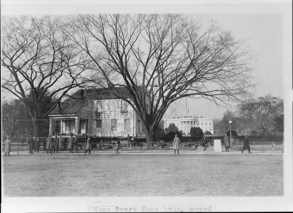 circa 1924: Moving a house in front of The White House in Washington, D.C.