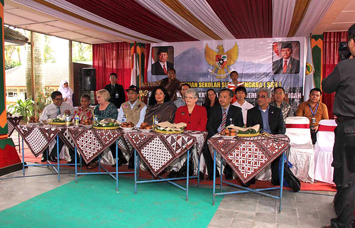 group listening to a presenter seated at tables with indonesian fabric decoration