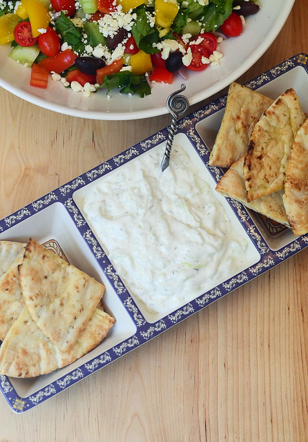 A serving platter with Toasted Pitas with Tzatziki Sauce.