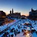 Photo of people skating on the Rideau Canal Skateway, Ottawa, during Winterlude with Parliament Hill in background. Photo de patineurs sur la patinoire du canal Rideau, à Ottawa, avec la colline du Parlement en arrière-plan, pendant le Bal de Neige.