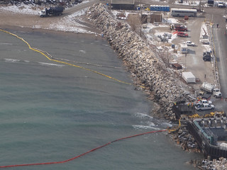 Cleanup crews work to deploy boom along the Lake Michigan shoreline to near the BP Whiting Refinery in Whiting, Ind., March 25, 2014, to recover crude oil discharged from the refinery.  Coast Guard pollution responders from Marine Safety Unit Chicago were on scene to monitor the ongoing recovery efforts with the Environmental Protection Agency and the Indiana Department of Environmental Management, as a helicopter crew from Coast Guard Air Station Traverse City, Mich., conducted an overflight to assess the extent of the discharge.  U.S. Coast Guard photo by Petty Officer 3rd Class Parker Wood.