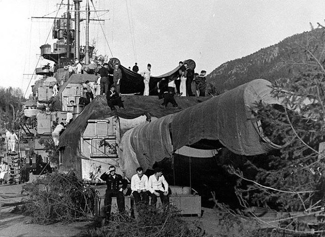 Sailors camouflaging the Tirpitz in a Norwegian fjord.
