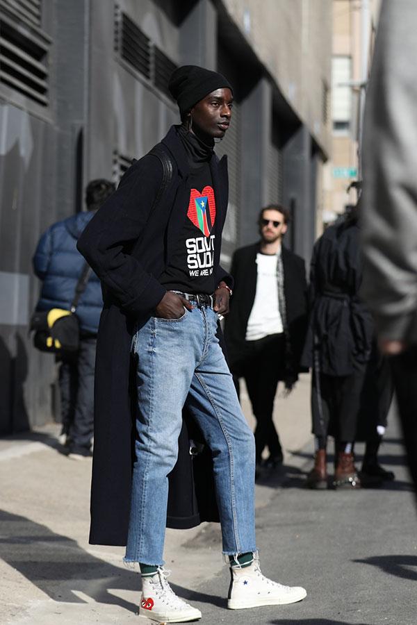 黒ニットキャップ×黒ロングコート×黒カットソー×ジーンズ×プレイコムデギャルソンのスニーカー白