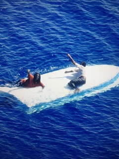 Two Bahamian citizens cling to the hull of their capsized vessel as a Coast Guard MH-65 rescue helicopter crew makes their approach to hoist them east of Riviera Beach, Fla., Saturday. The two people were found after drifting for approximately eight days. (U.S. Coast Guard photo.)
