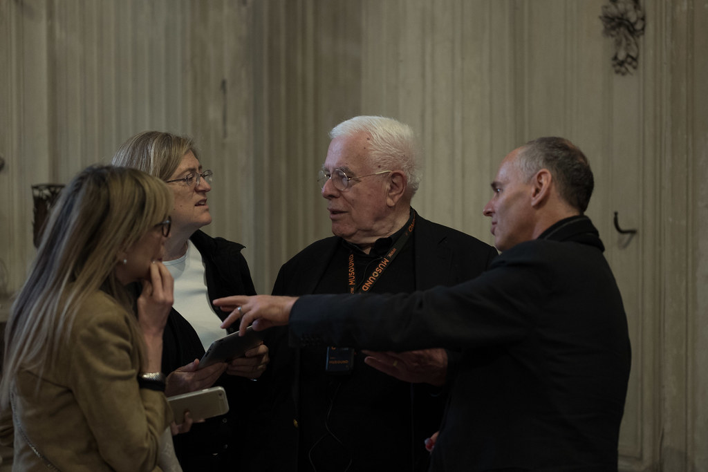 Peter Eisenman (B.Arch. '55), center, and Gale and Ira Drukier Dean of AAP Kent Kleinman, right, speak with guests at the Sala della Protomoteca.  photo / Don Randel, former Cornell provost