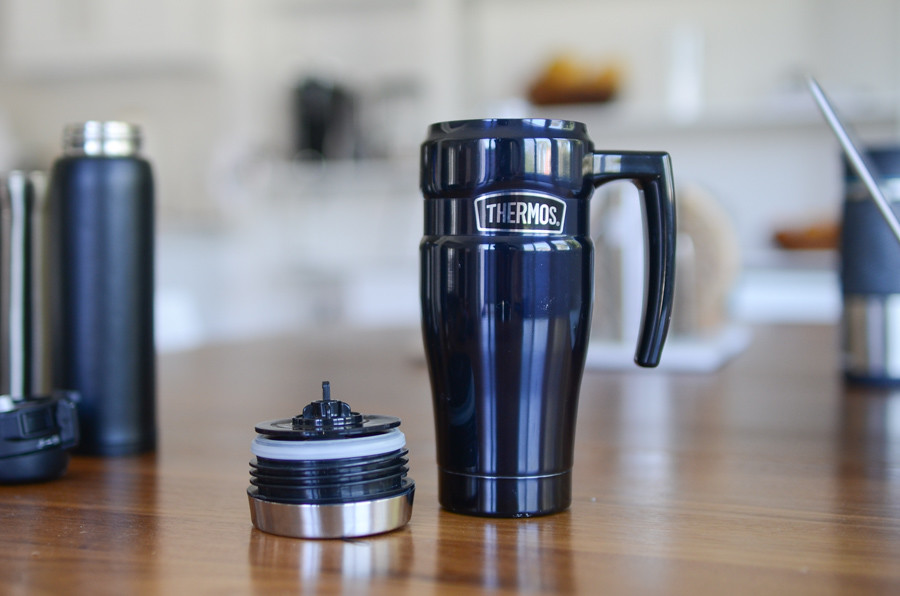 blue Thermos coffee / tea travel mug on table