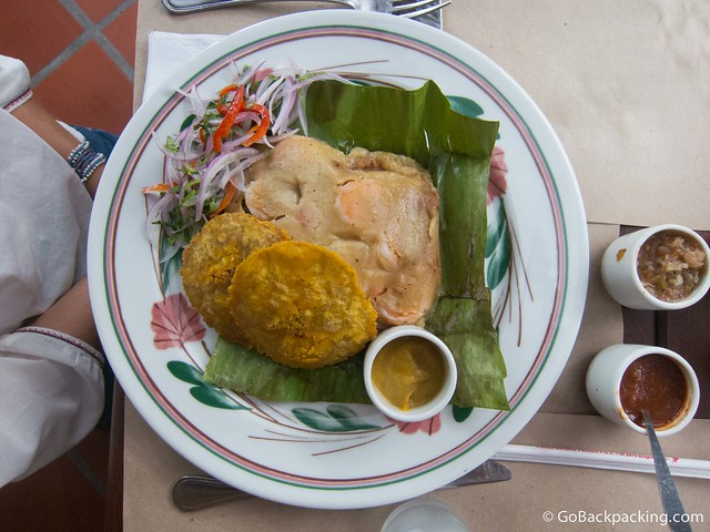 Tamale filled with fish, shrimp, coconut and spices, with a side of salsa de lulo