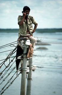 Telephone technician checking lines. Savar region, north of Dhaka. Bangladesh 2004. Photo: Heldur Netocny