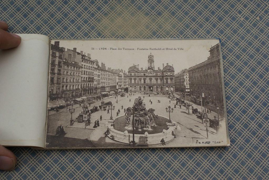 > Place des Terreaux à Lyon au début du 20e siècle avec la fontaine Bartholdi et l'Hotel de Ville.