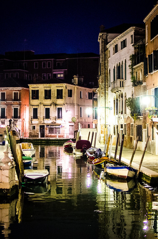 A quiet canal at night in Venice.