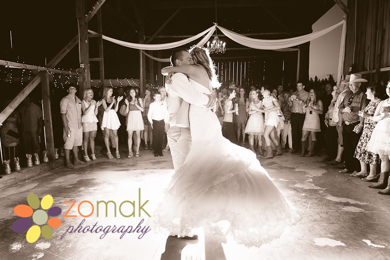 Groom swings bride around the dance floor at their country wedding.