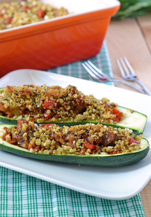 Two stuffed zucchini halves on a white plate