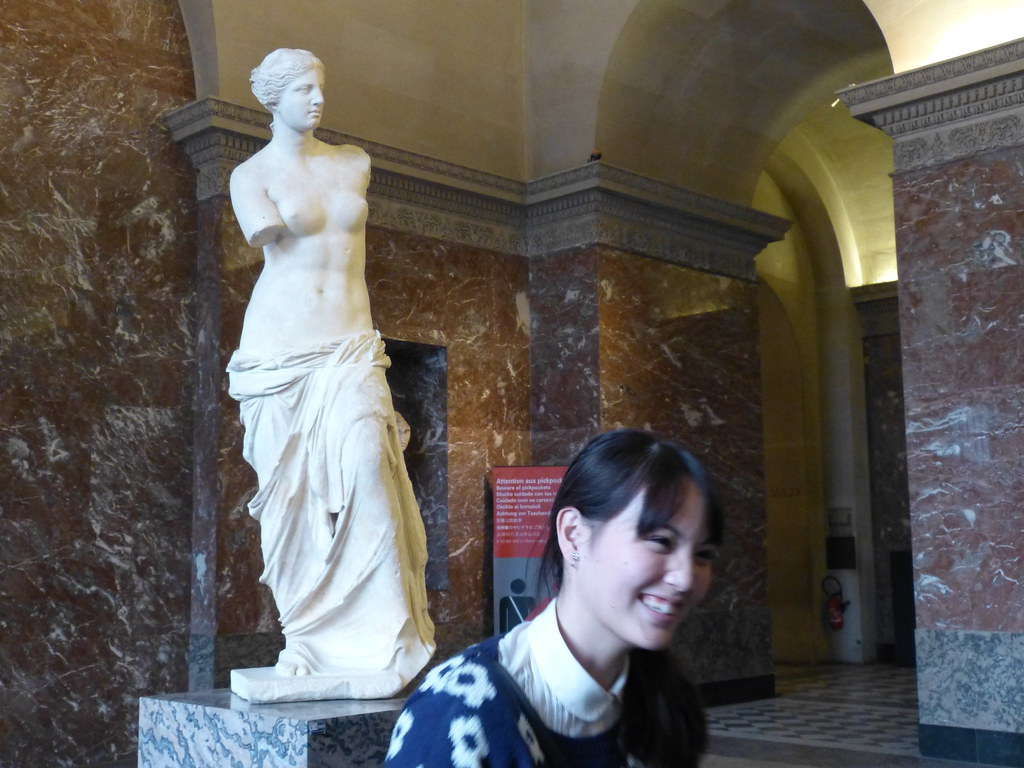 Girl posing in fron of the Venus of Milo, Louvre Museum