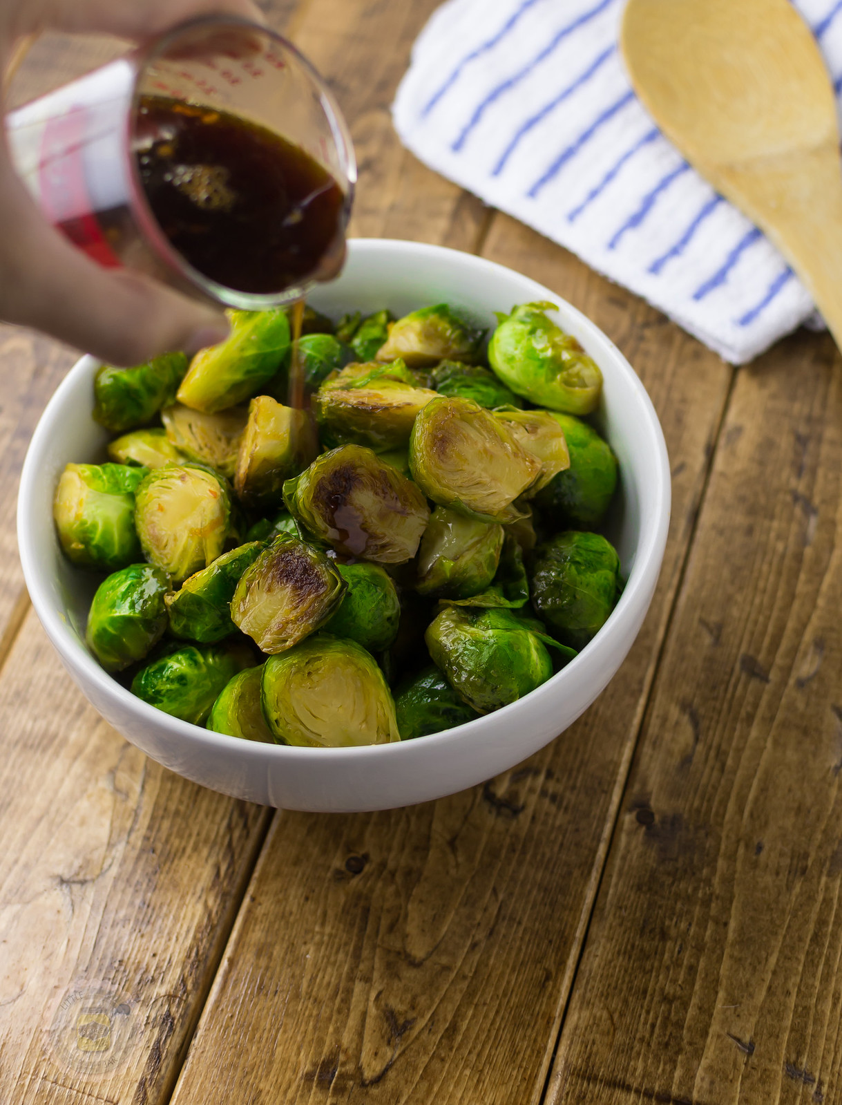 pouring prepared sauce from measuring cup over Brussel sprouts in white bowl on wood surface