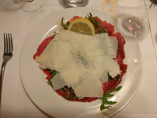 beef carpaccio hiding under a mound of fresh parmesan