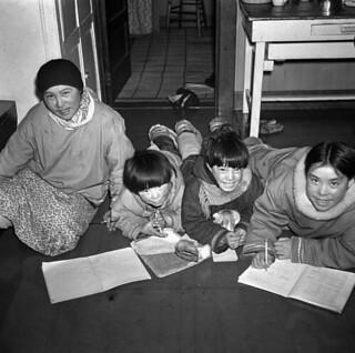 Inuit children studying in the kitchen of Reverand W. J. R. James of St. Aidan's Anglican Mission... / Des enfants inuits étudiant dans la cuisine du révérend W. J. R. James de la mission anglicane de St. Aidan...