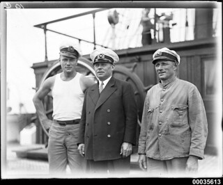 Captain Lorenz Peters with crew members near the ship's wheel on MAGDALENE VINNEN