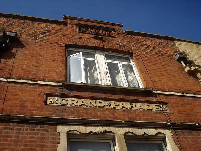 The top floor of a brick building, with a bas-relief saying 'GRAND PARADE'.  The bas-relief has a floral motif in between the words and leaf motifs at either end.  The sky is visible at the top, a clear deep blue.