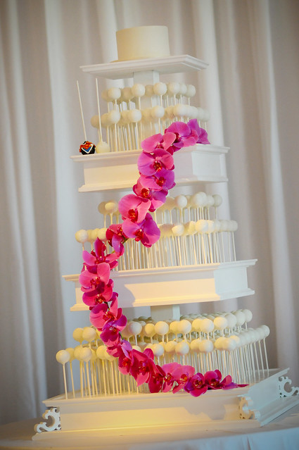 Our custom tiered white cake pop stand decorated with flowers in lieu of a traditional cake.