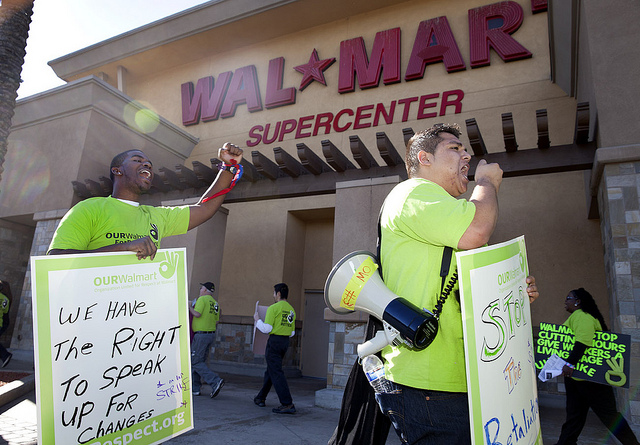 Two protesters march outside of Walmart.