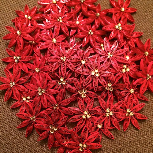 Quilled red poinsettias with yellow crystal centers