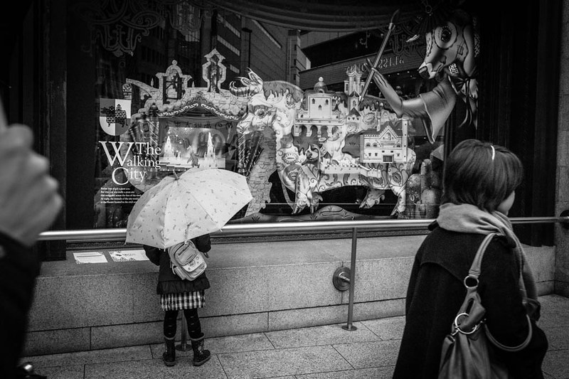 Little girl with umbrella at a store window.