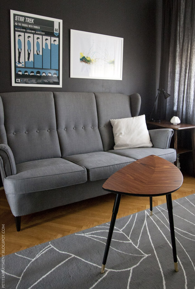 mid century modern living room with grey strandmon sofa wooden table and dark grey black wall with star trek poster  inspiration
