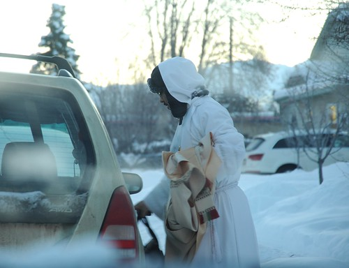 Priest wearing arctic winter whites carrying his vestments and bag, going to the Alaska Pioneer's Home to say Mass, snow, South Addition, Anchorage, Alaska, USA by Wonderlane