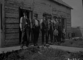 Six men and two boys standing outside a Hudson's Bay Company post, Fort Providence, Northwest Territories / Six hommes et deux garçons debout devant un poste de la Compagnie de la Baie d'Hudson, Fort Providence (Territoires du Nord-Ouest)