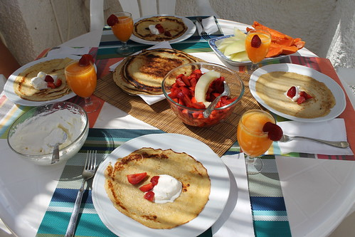 Crepes with whipped cream, sliced strawberries, freshly cut papaya and melon and freshly squeezed orange juice