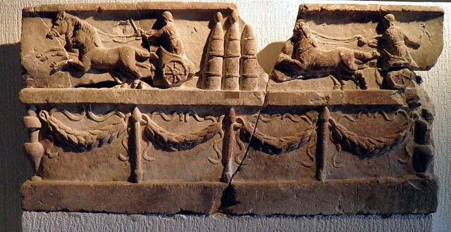 Limestone bas-relief with scene of chariots at full rush, in the centre three boundary stones and below a balustrade decorated with laurel leaves garlands, Musée gallo-romain de Fourvière, Lyon