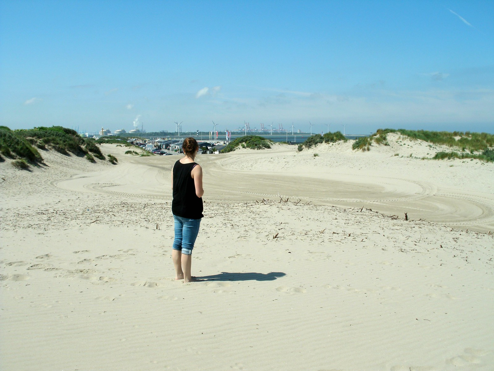 A barefoot girl at the beach looks over at the windmills in the distance.