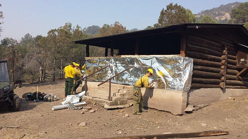 Forest Service firefighters wrap a cabin in Aluminized Structure Wrap to protect the building from radiant heat and burning embers from the Silver Fire on the Gila National Forest in 2012. Wrapping a structure is the best protection strategy when it's too dangerous to stay. (US Forest Service photo)