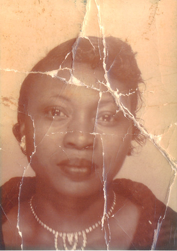 A faded photo of the author's grandmother, a black woman wearing a pearl necklace and beautiful earrings