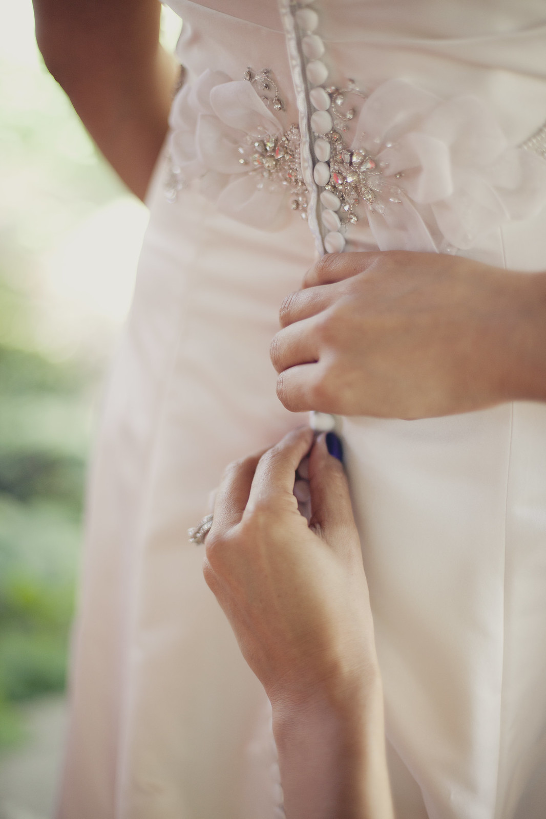 Buttoning up a beautiful wedding dress before the ceremony