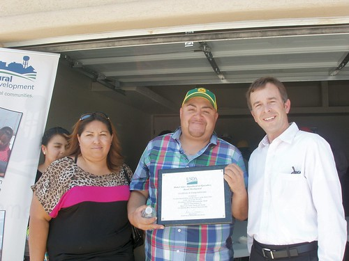 New Mexico USDA Rural Development  State Director Terry Brunner (r) presents a certificate of congratulations to Sandra and Miguel Duarte.  The presentation was made during National Homeownership Month event in Sunland Park to honor the Durate family for becoming new homeowners. USDA photo.