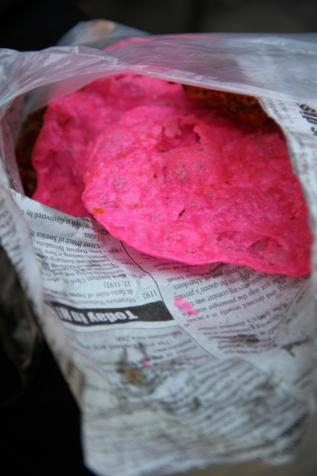 Pink puris wrapped in newspaper