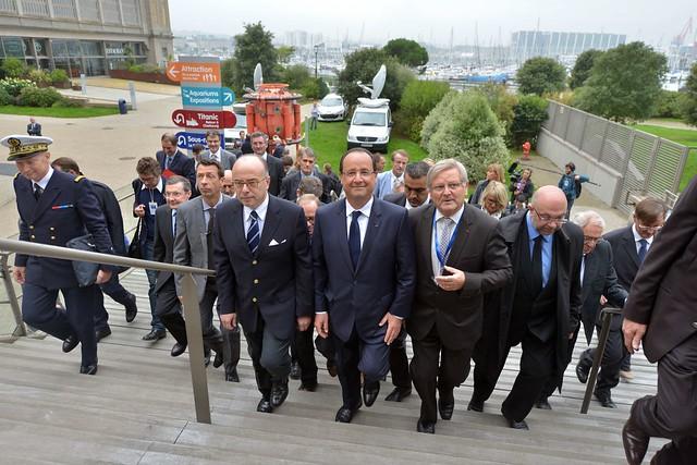 François Hollande arrive à la cité de la mer accompagné de Bernard Cauvin, président de la Cité de la Mer (à droite), Bernard Cazeneuve, ministre du Budget (à gauche)