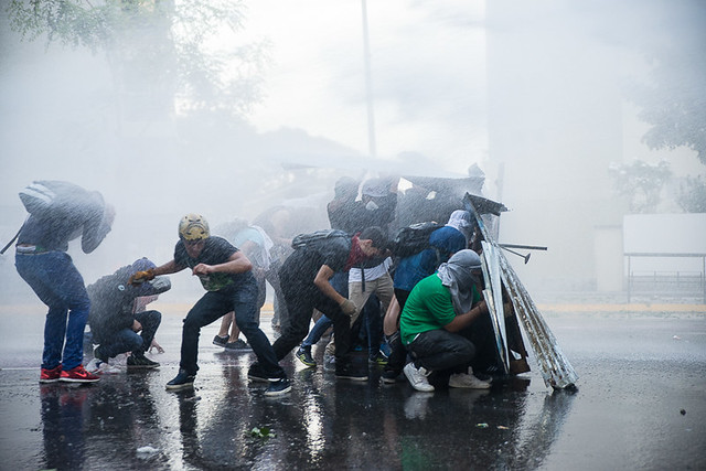 protestors being sprayed by a water cannon