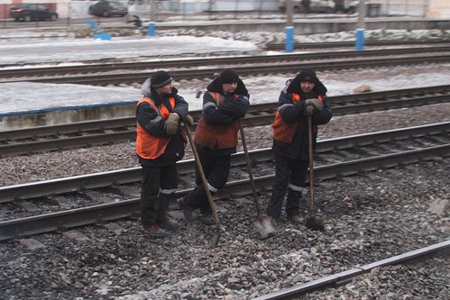Stereotypical workers: leaning on their shovels, as they wait for our train to pass