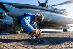 Sailor attaches chain to pad eye aboard USS Germantown.
