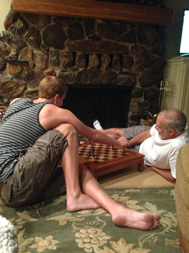 A young man and his father sitting on the floor playing chess in front of a fireplace.