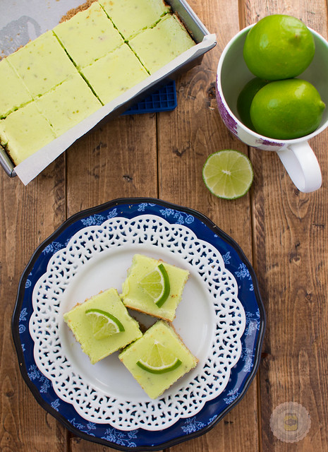 cut squares of key lime pie squares on plate topped with lime wedges
