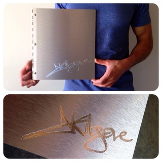 Custom graphic design portfolio book in brushed silver aluminum with silver on silver engraving