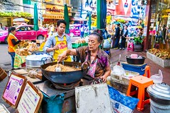 Busy Bangkok street corner with asian woman cooking on wok.