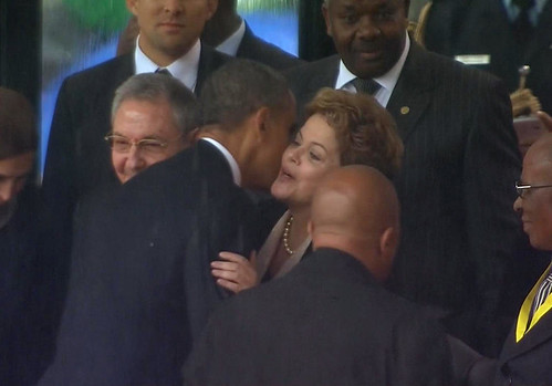 United States President Barack Obama embracing Brazil President Dilma Rousseff after shaking hands with President Raul Castro of Cuba. They all attended the Mandela memorial. by Pan-African News Wire File Photos