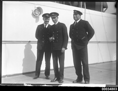 Three officers on the deck of a ship