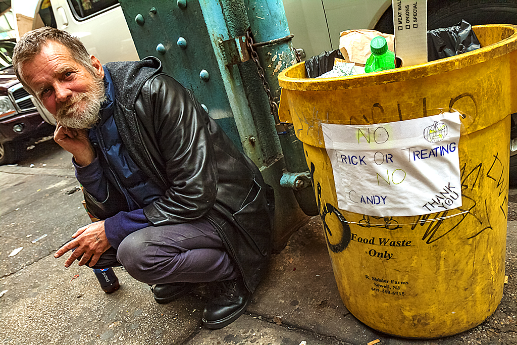 Man-squatting-by-trash-can--Kensington