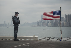 Fire Controlman 2nd Class Bill Alexander stands watch as USS Makin Island (LHD 8) sits at anchor in Hong Kong, April 7. (U.S. Navy/MC3 Devin M. Langer)